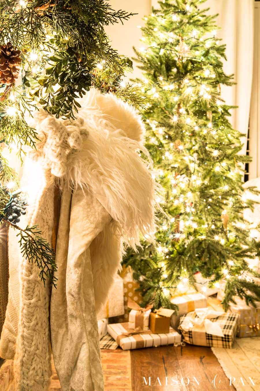white fur stockings and greenery by tree with lights | Maison de Pax