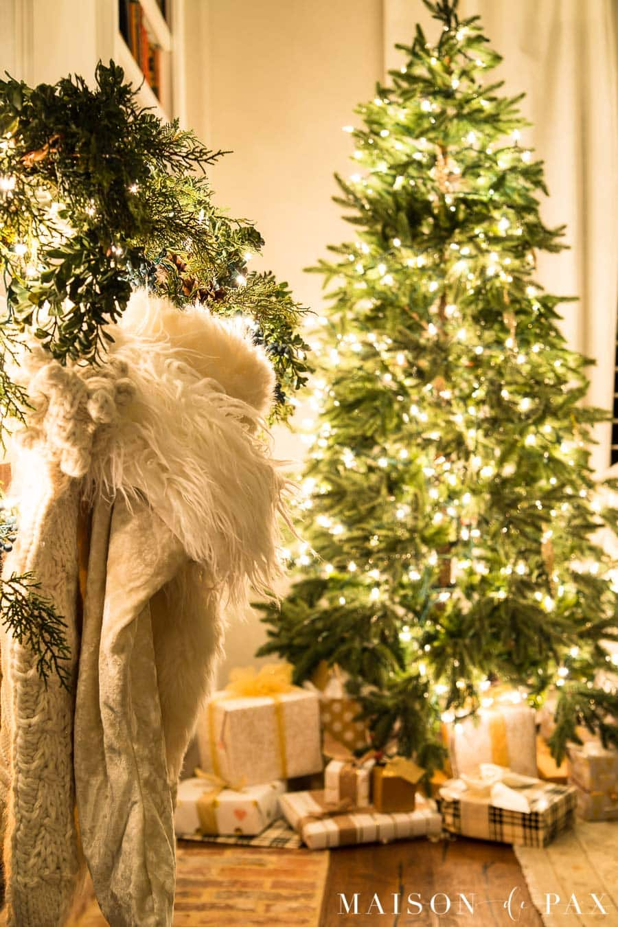 white fur stockings and beautifully wrapped presents under almost naked Christmas tree at night | Maison de Pax