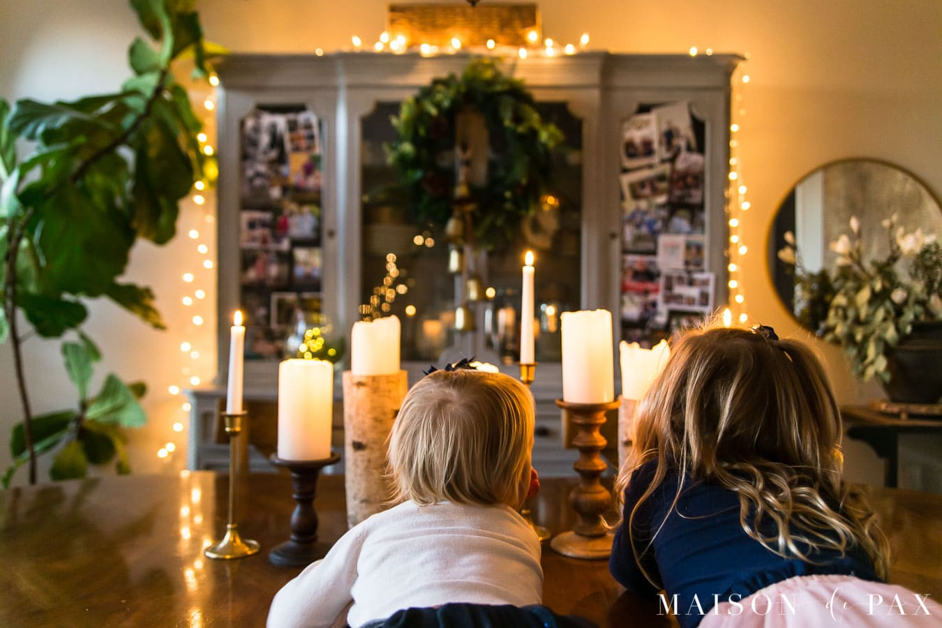 girls looking at candles in Christmas dining room | Maison de Pax