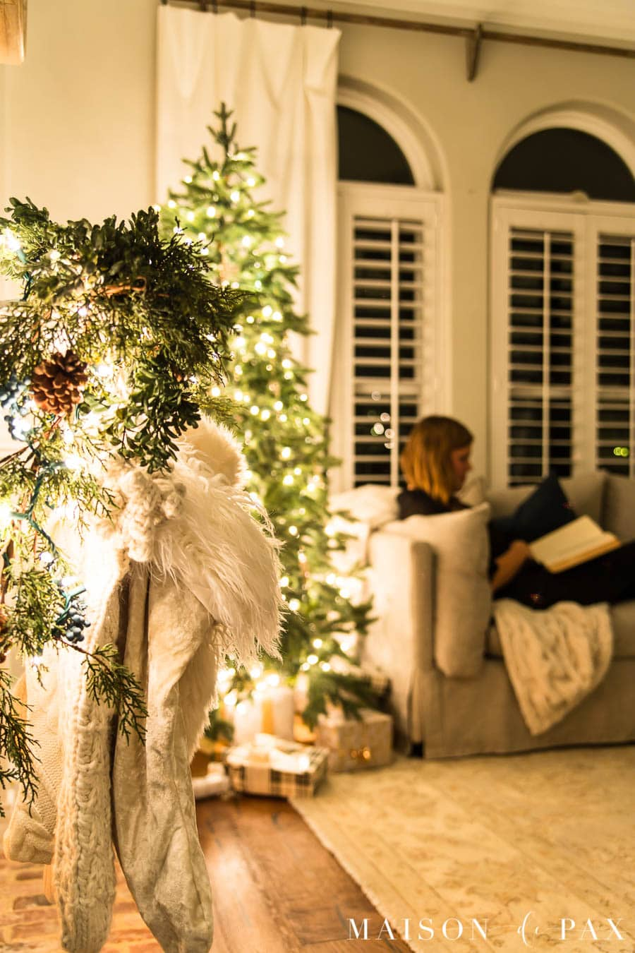 woman reading on couch beside Christmas tree at night | Maison de Pax