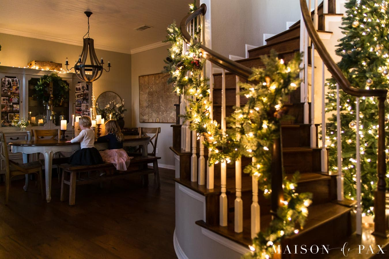 curved stairwell with lit garland by dining room | Maison de Pax