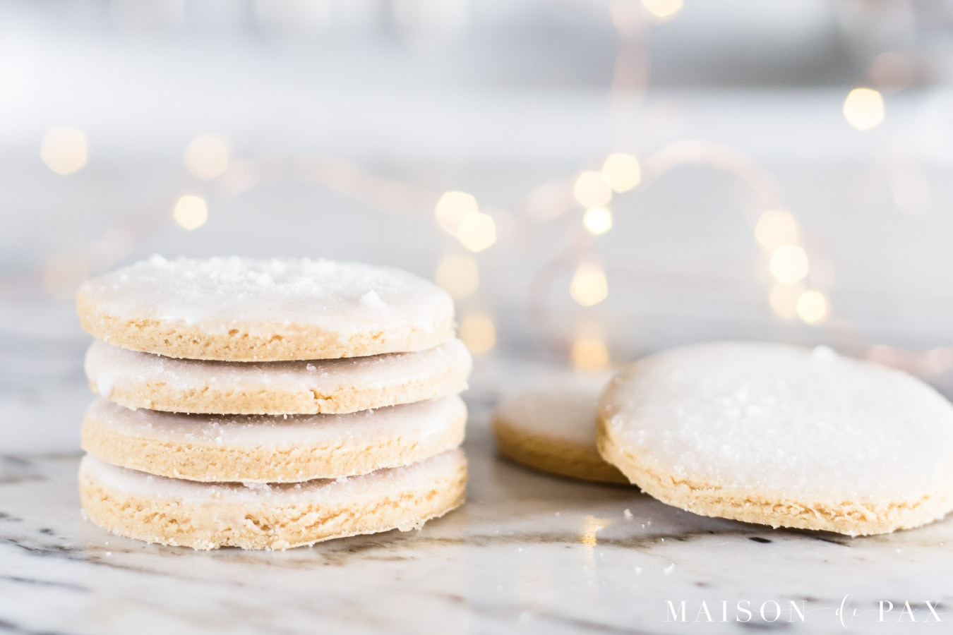 stacked iced cookies with sugar sprinkled on top and christmas lights | maison de pax