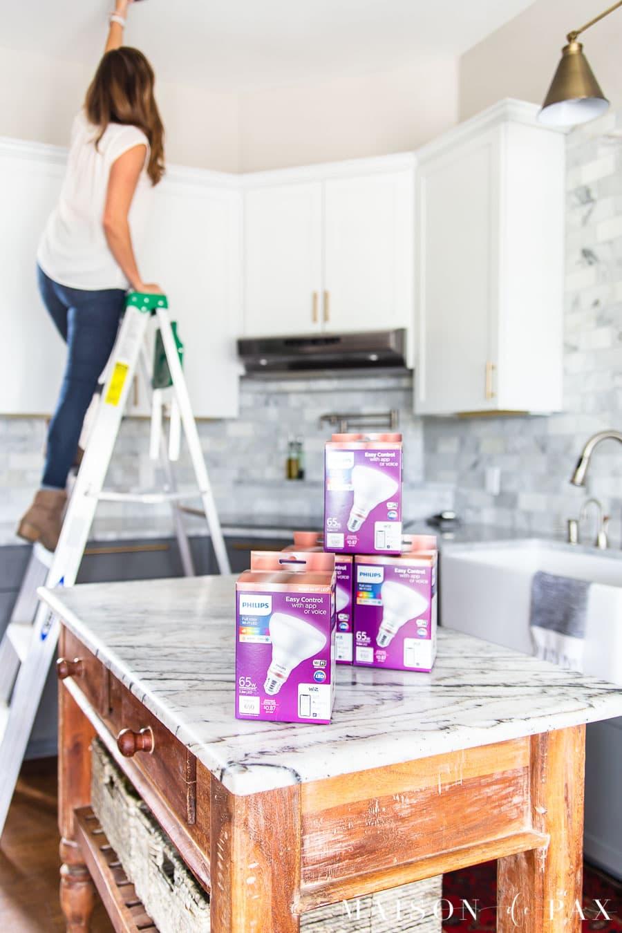 woman installing smart bulbs | Maison de Pax
