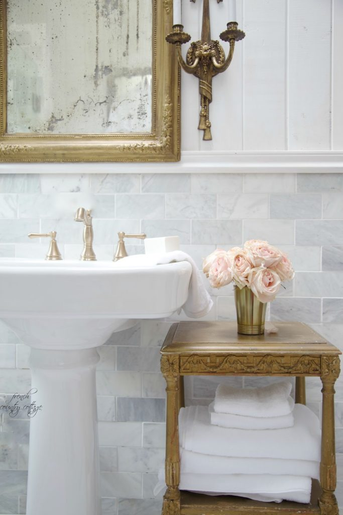 gold leaf mirror, antique washstand, and marble wall tile