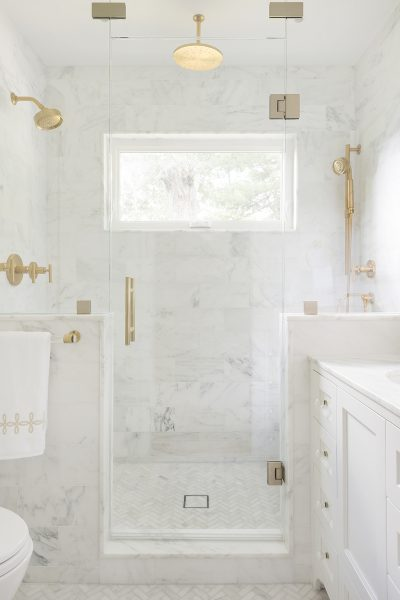 marble walk in shower with gold hardware and gold shower faucets