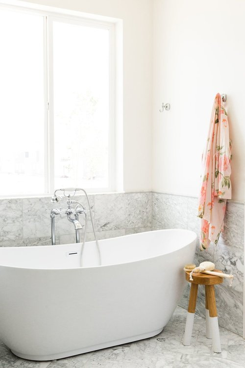 white modern freestanding tub and large marble wall tile