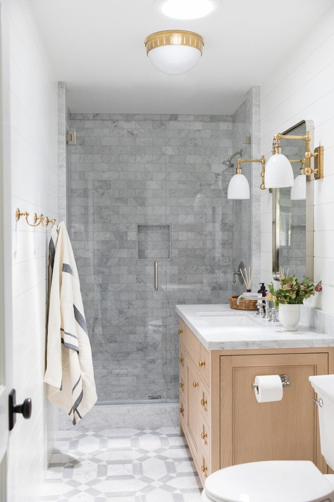 bathroom with patterned marble floor tile and marble subway wall tile with light wood vanity and mixed metals
