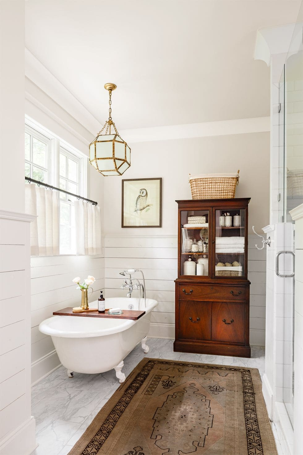 marble floors, antique wood cabinet, and clawfoot tub