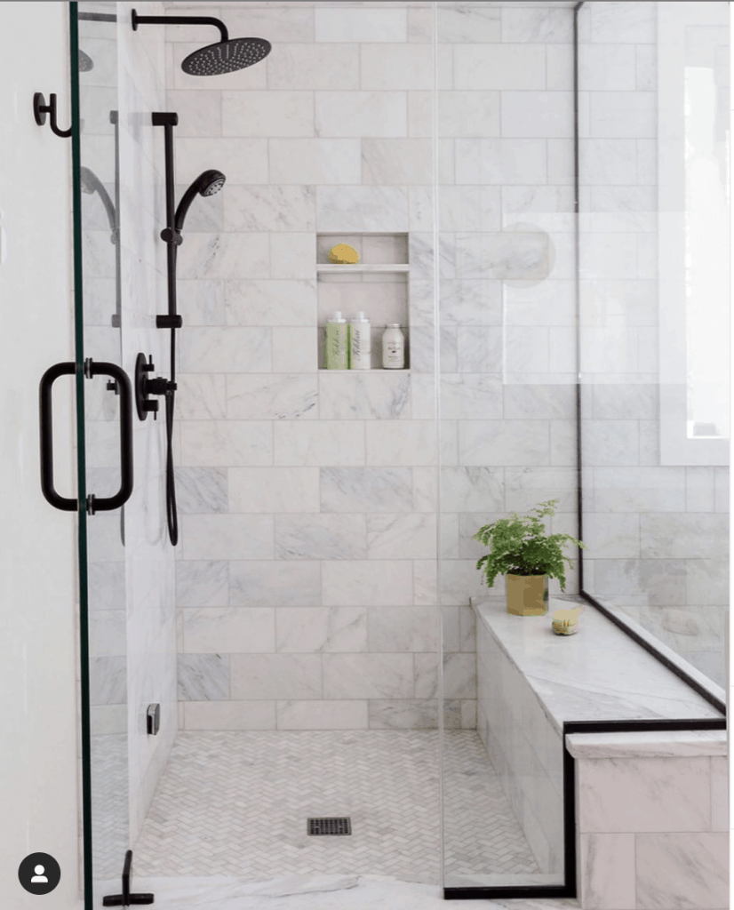 carrara marble shower with black plumbing fixtures and shower door frame