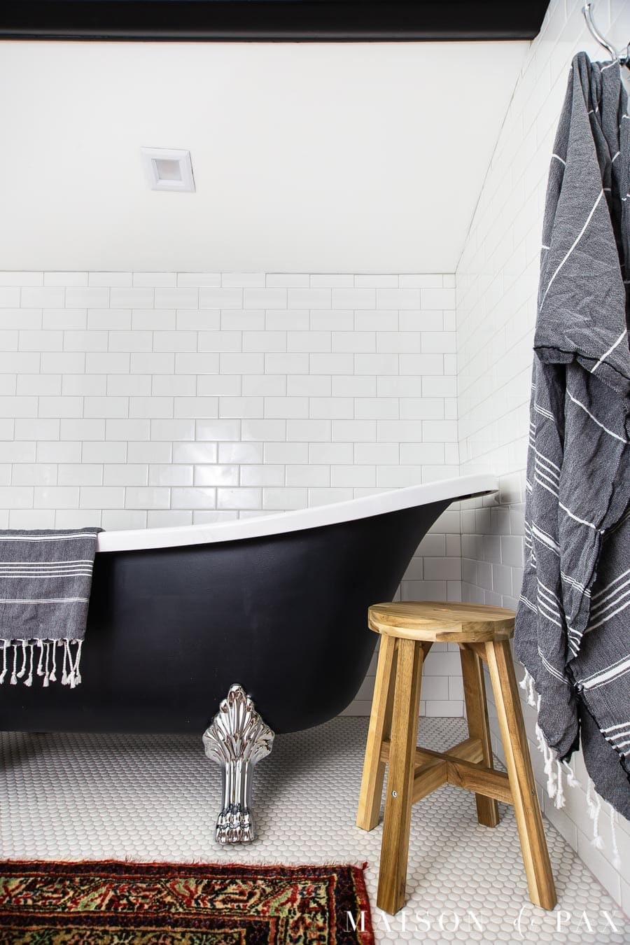 black clawfoot tub with chrome legs and a wooden stool | Maison de Pax