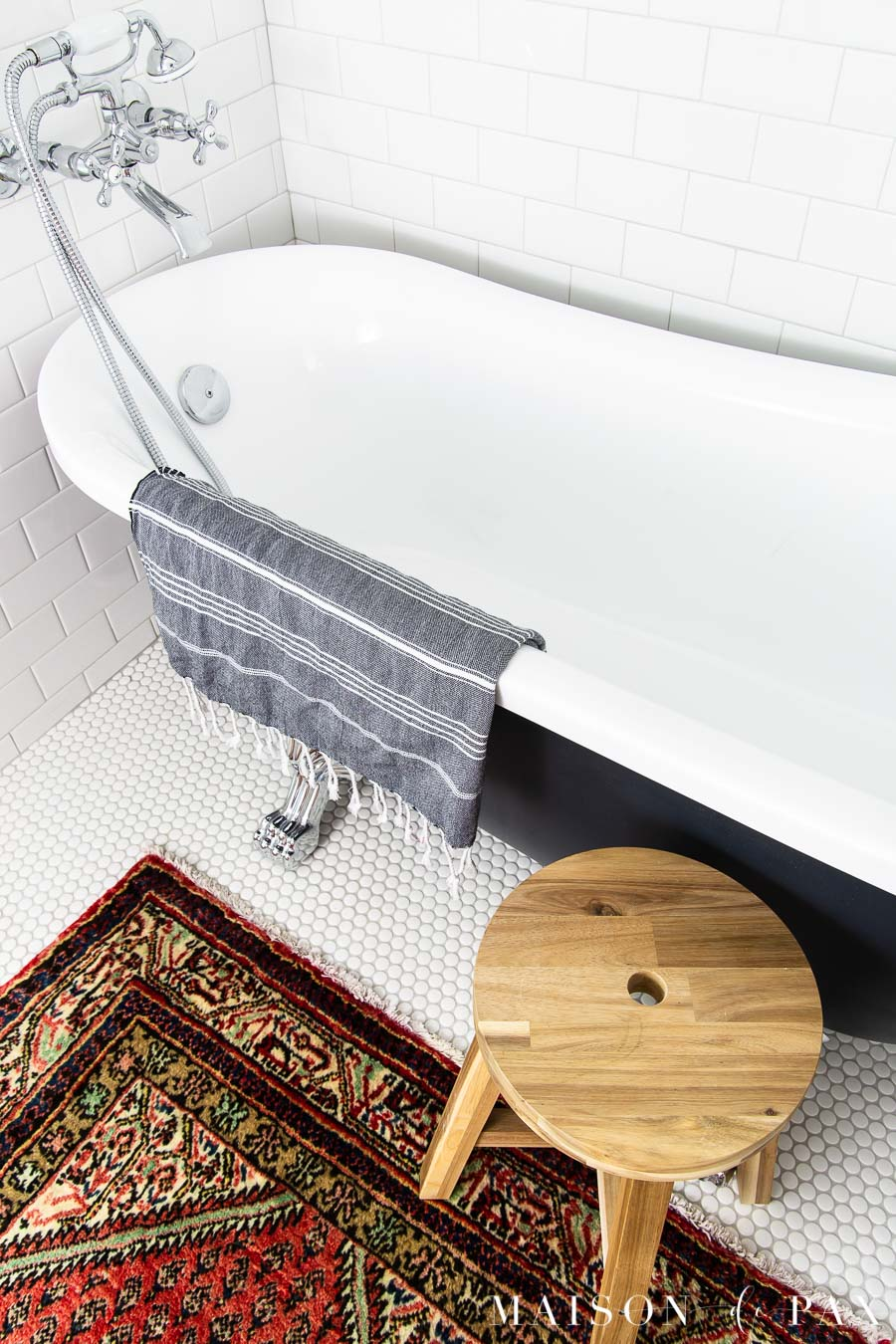 white penny tile on floor beneath black clawfoot tub | Maison de Pax