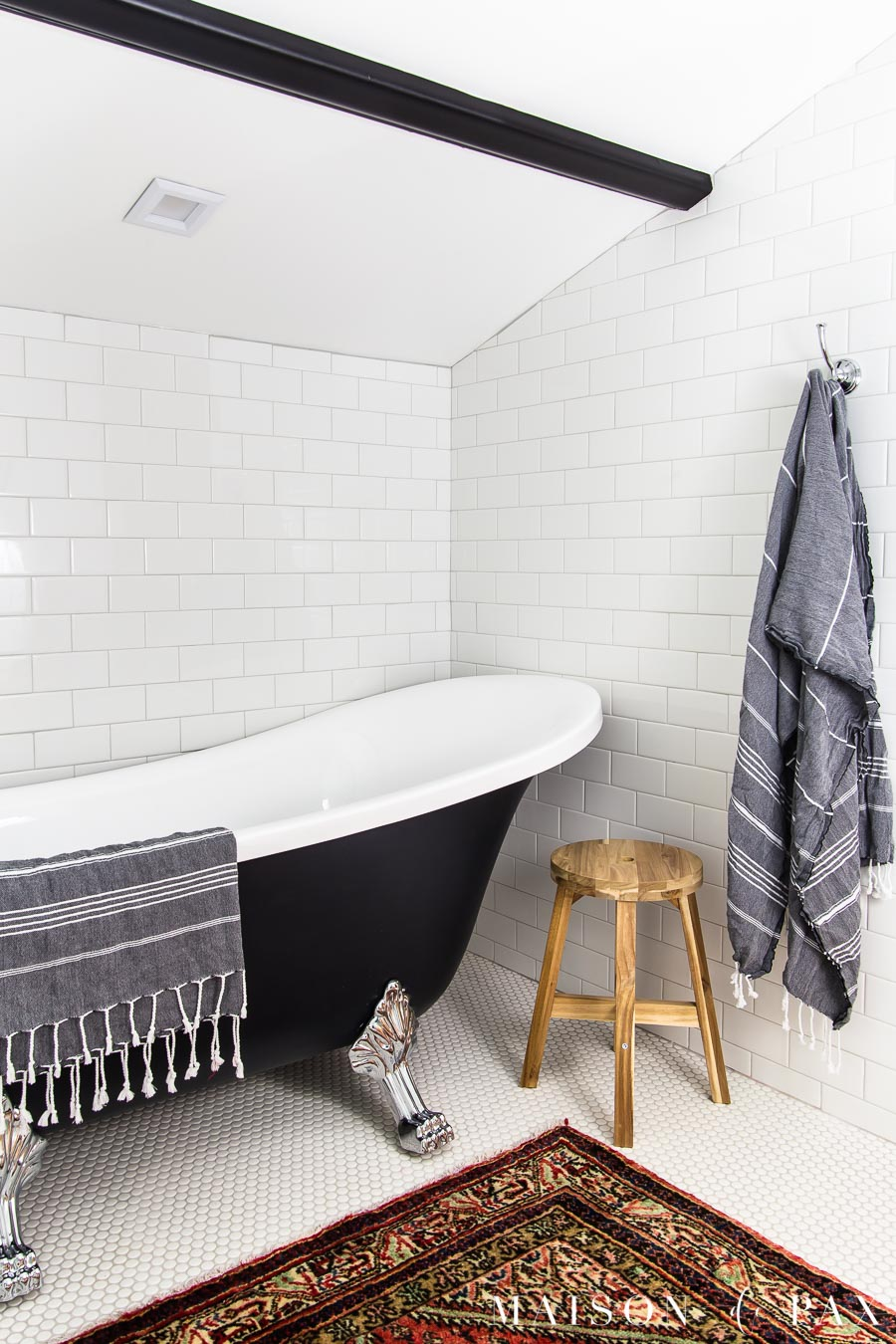 low angled ceiling above clawfoot tub in classic black and white bathroom | Maison de Pax