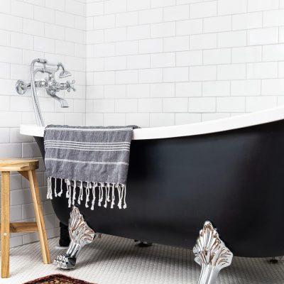 black clawfoot tub with chrome feet in white tile bathroom   Maison de Pax