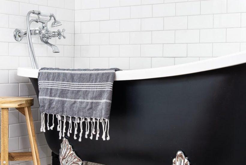 black clawfoot tub with chrome feet in white tile bathroom | Maison de Pax