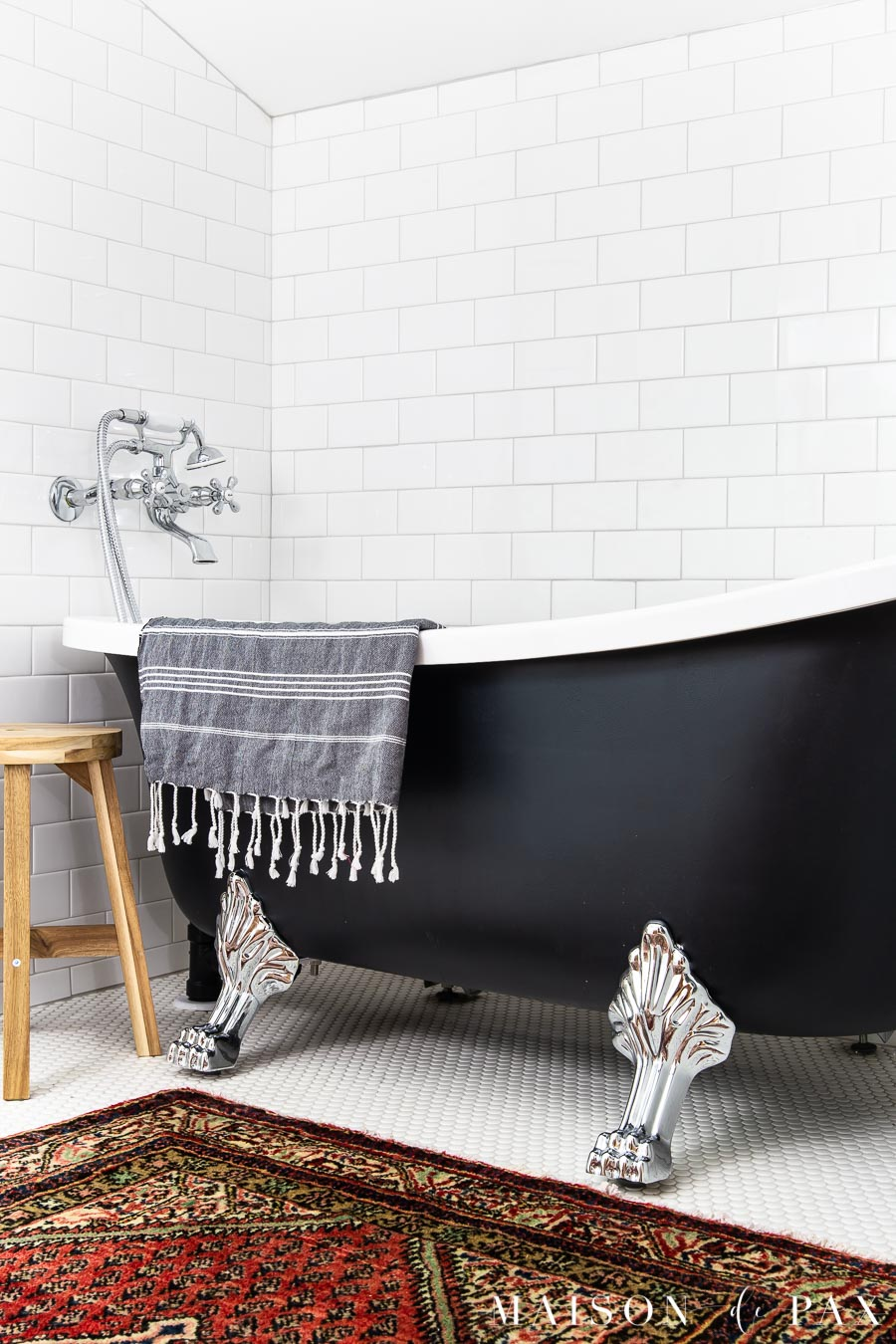 black clawfoot tub with chrome feet in white tile bathroom | Maison de Pax