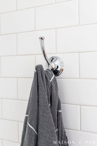 chrome towel hook on white subway tile wall