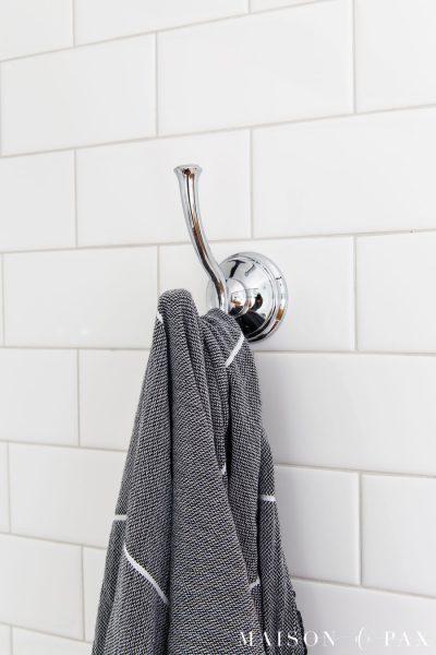 chrome towel hook on white subway tile wall