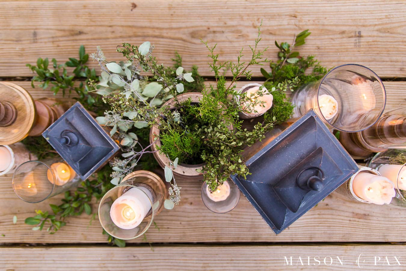 rustic dining table with centerpiece of wooden candlesticks, lanterns, and glass vases | Maison de Pax