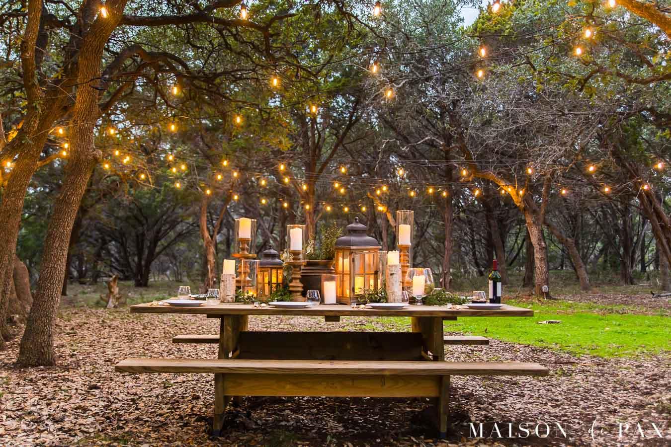 enormous picnic table with gorgeous centerpiece and string lights | maison de pax