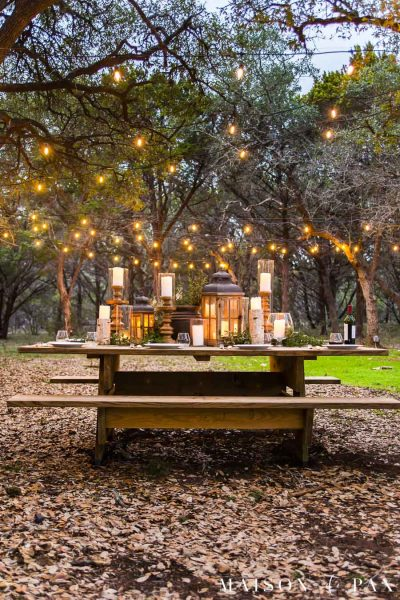 outdoor dining area: picnic table with lots of candles and string lights | maison de pax