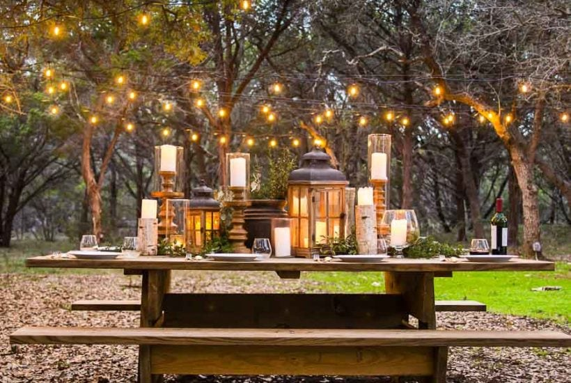 outdoor dining area: picnic table with lots of candles and string lights   maison de pax