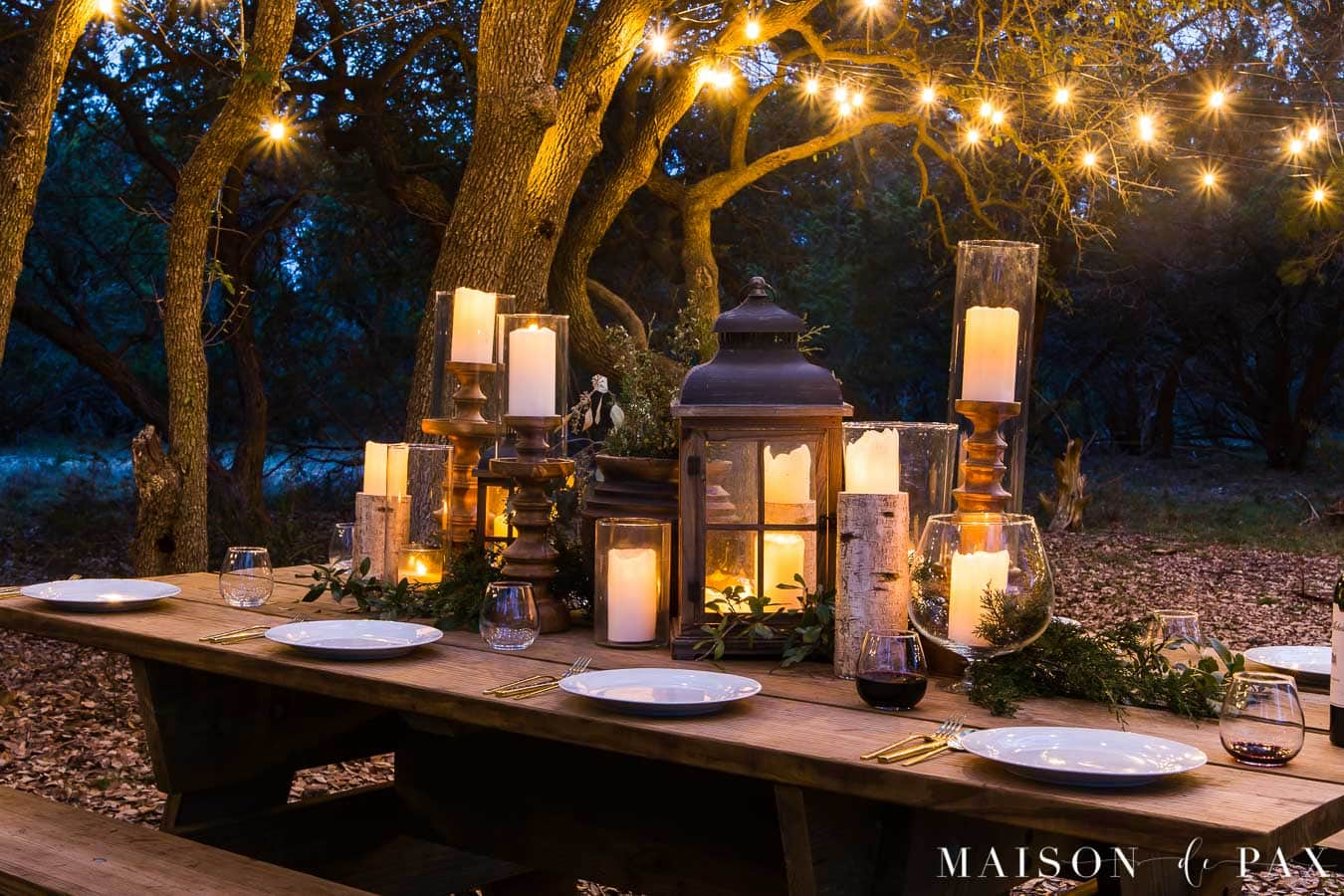 Create a rustic outdoor wedding table with candles, string lights, and greenery - Maison de Pax