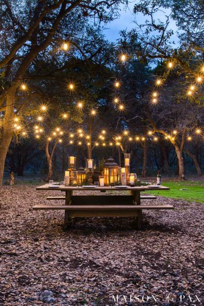 picnic table with globe string lights hanging above | Maison de Pax