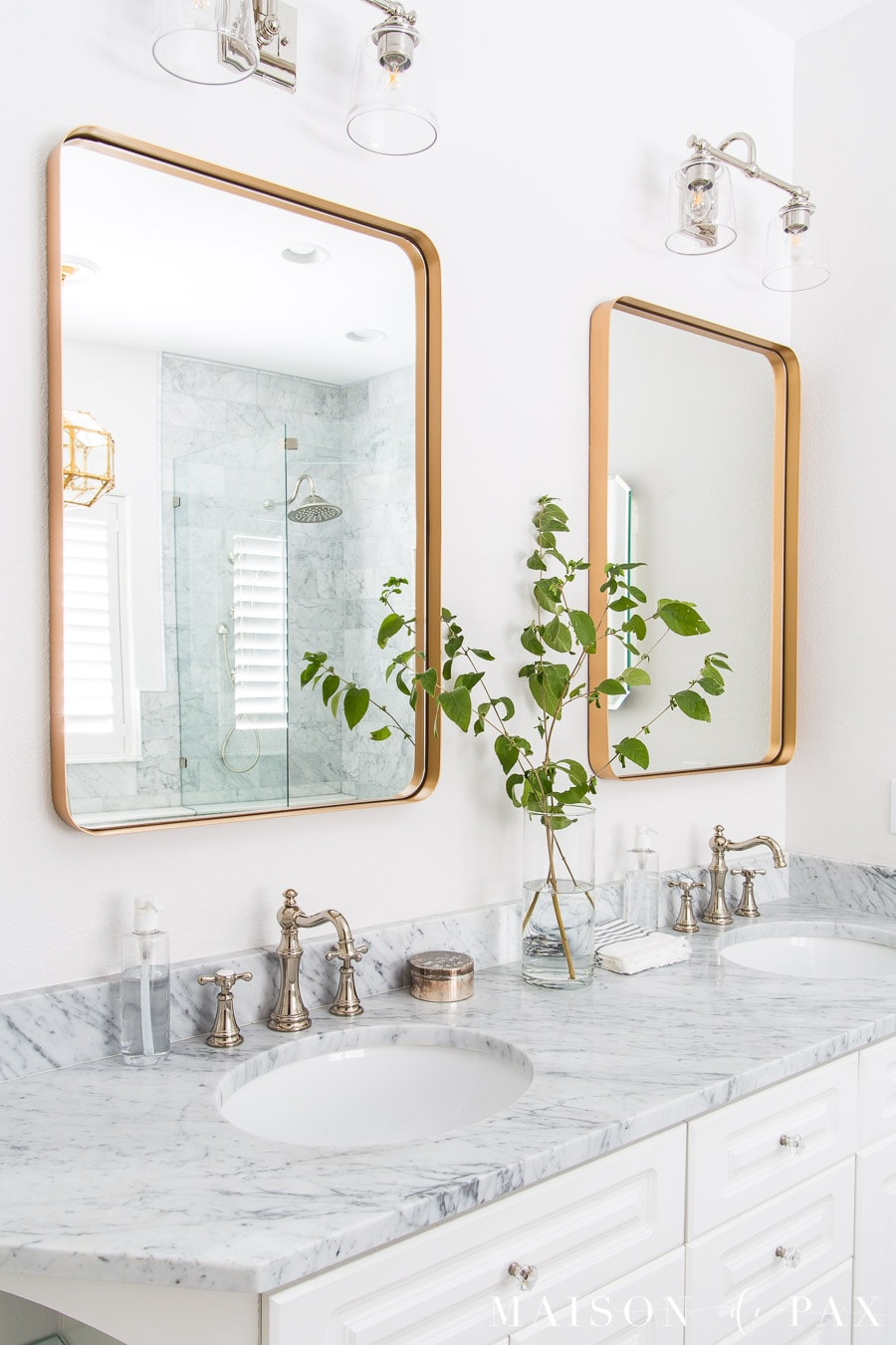Gold vanity mirrors and a Carrara marble vanity in a transitional master bathroom- Maison de Pax