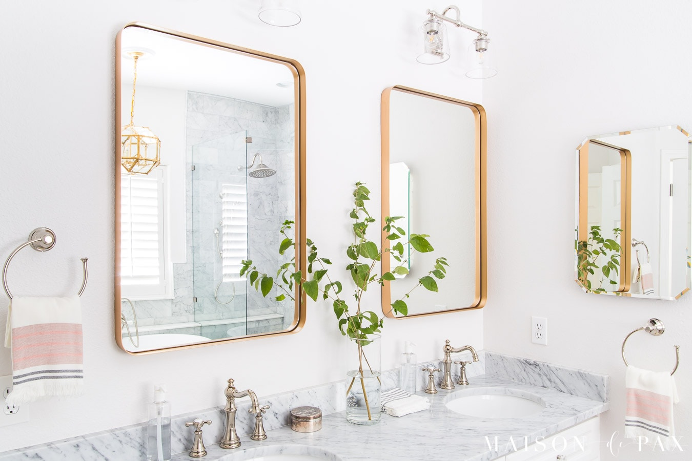 mid century metal gold mirrors, marble counters, and white cabinets in bathroom | Maison de Pax