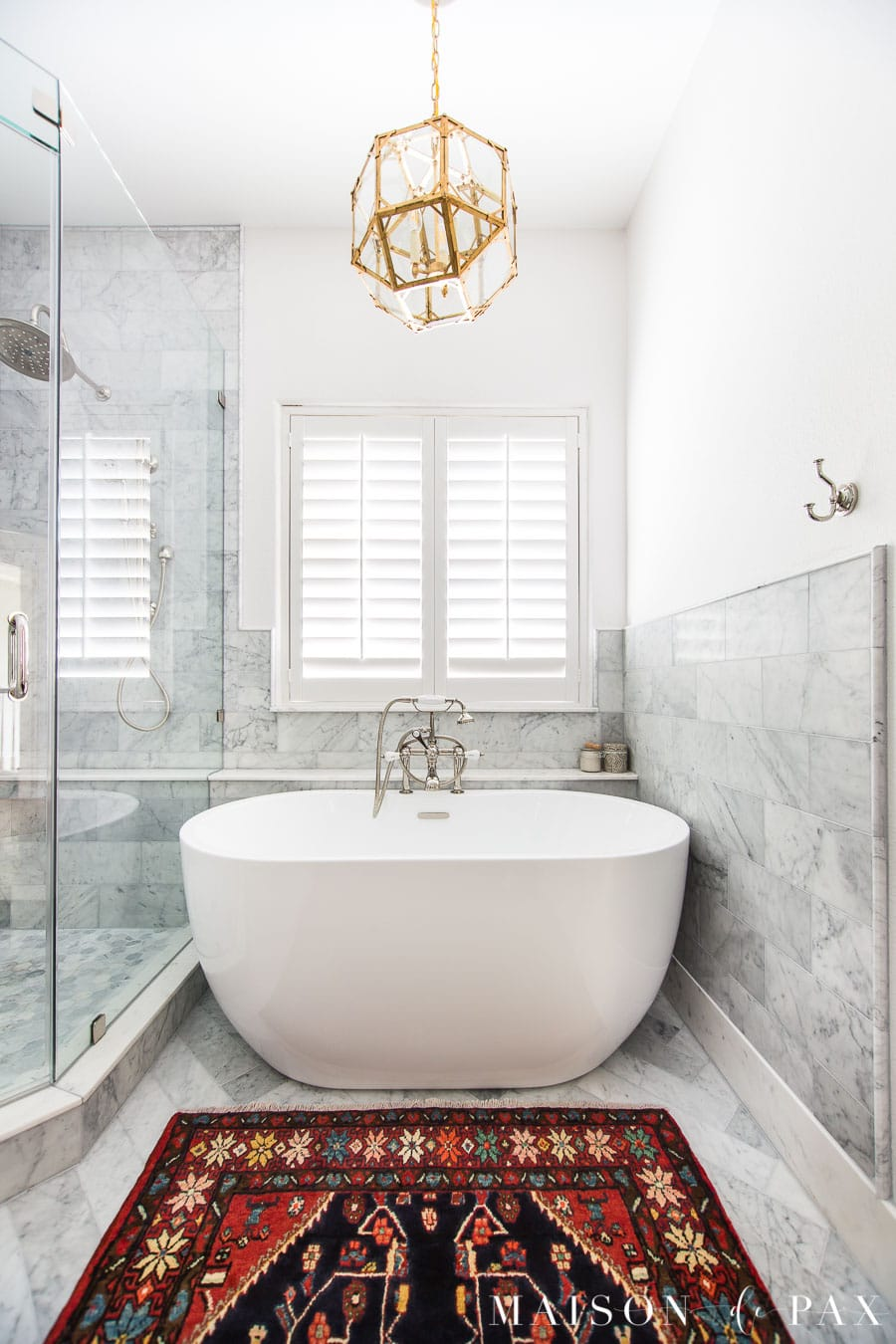 marble bathroom with white freestanding transitional tub and vintage rug | Maison de Pax