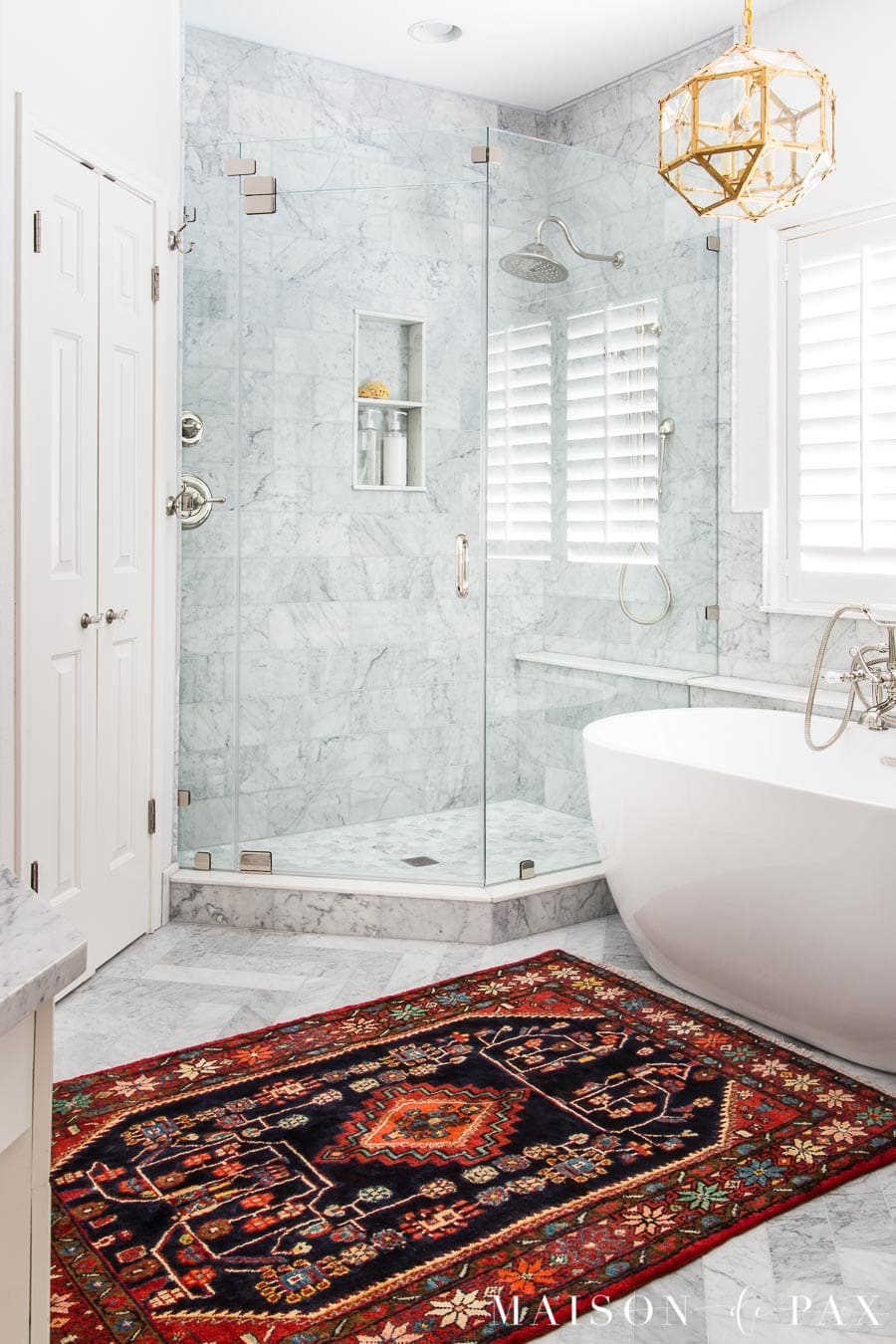 colorful vintage rug of Persian origin in marble master bathroom | Maison de Pax