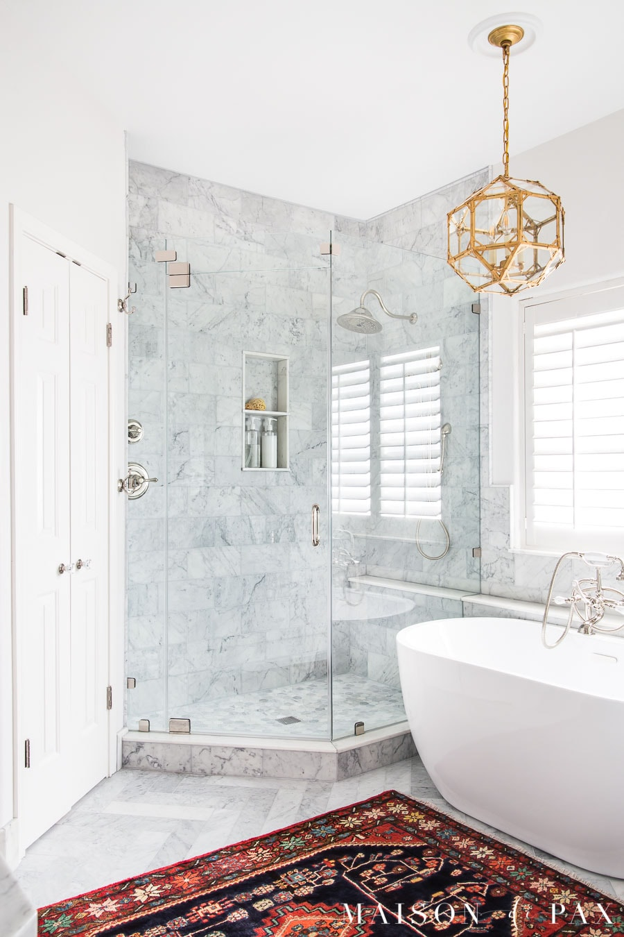 white bathroom with marble tile and freestanding tub with gold lighting | Maison de Pax