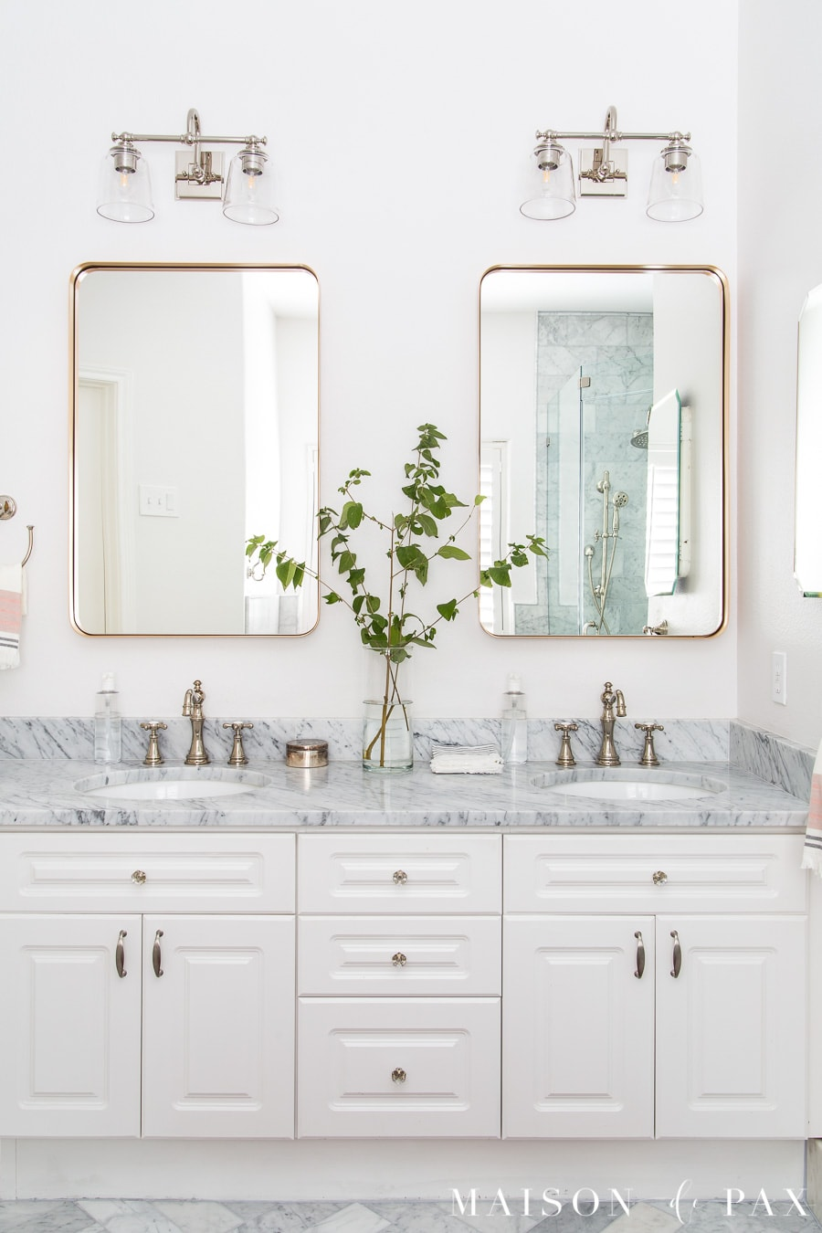 bath with marble counters, white vanity, polished nickel faucets, and gold mirrors | Maison de Pax
