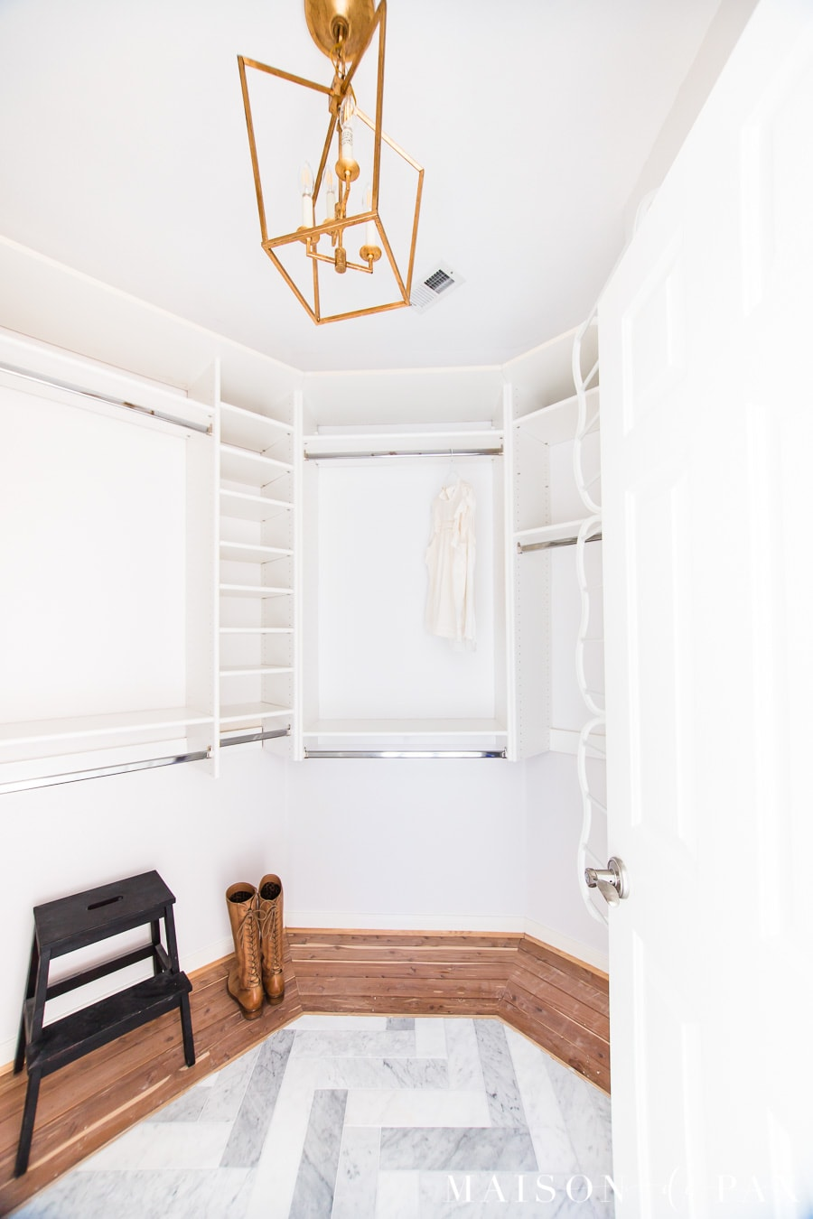 master closet with built in shelves, marble and cedar floors, and gold lantern chandelier | Maison de Pax
