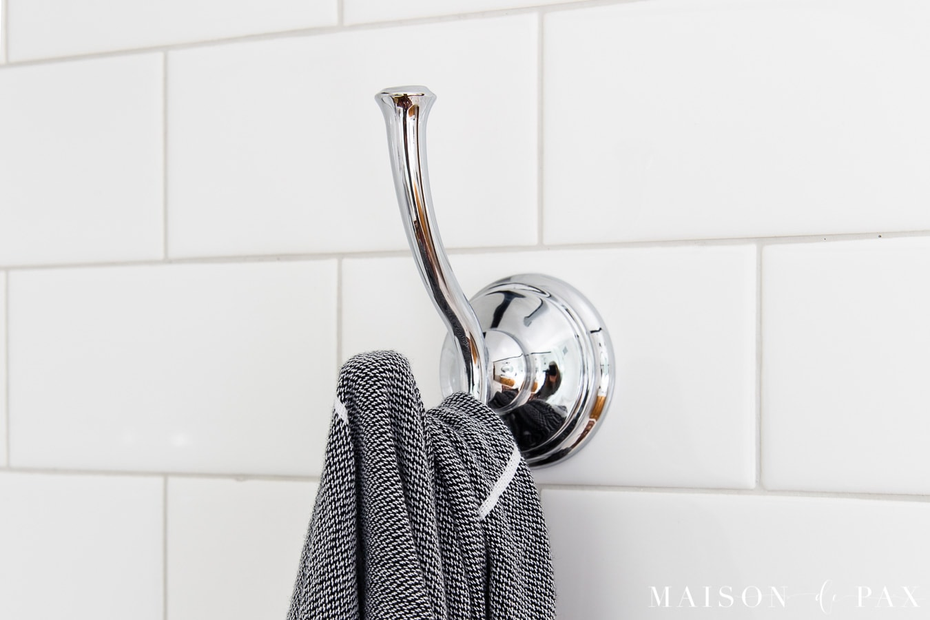 white subway tile wall with chrome hook for towels- Maison de Pax