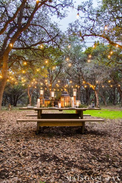 picnic table with beautiful centerpiece and string lights