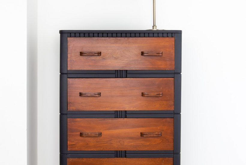four drawer tall black dresser with warm brown wood drawers
