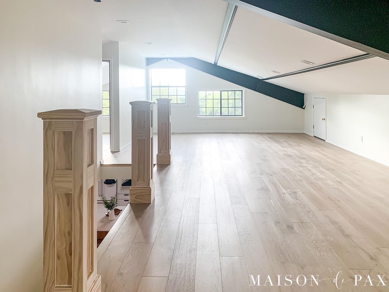 built out attic with windows, white oak floors, sloped ceilings, and black beams | Maison de Pax