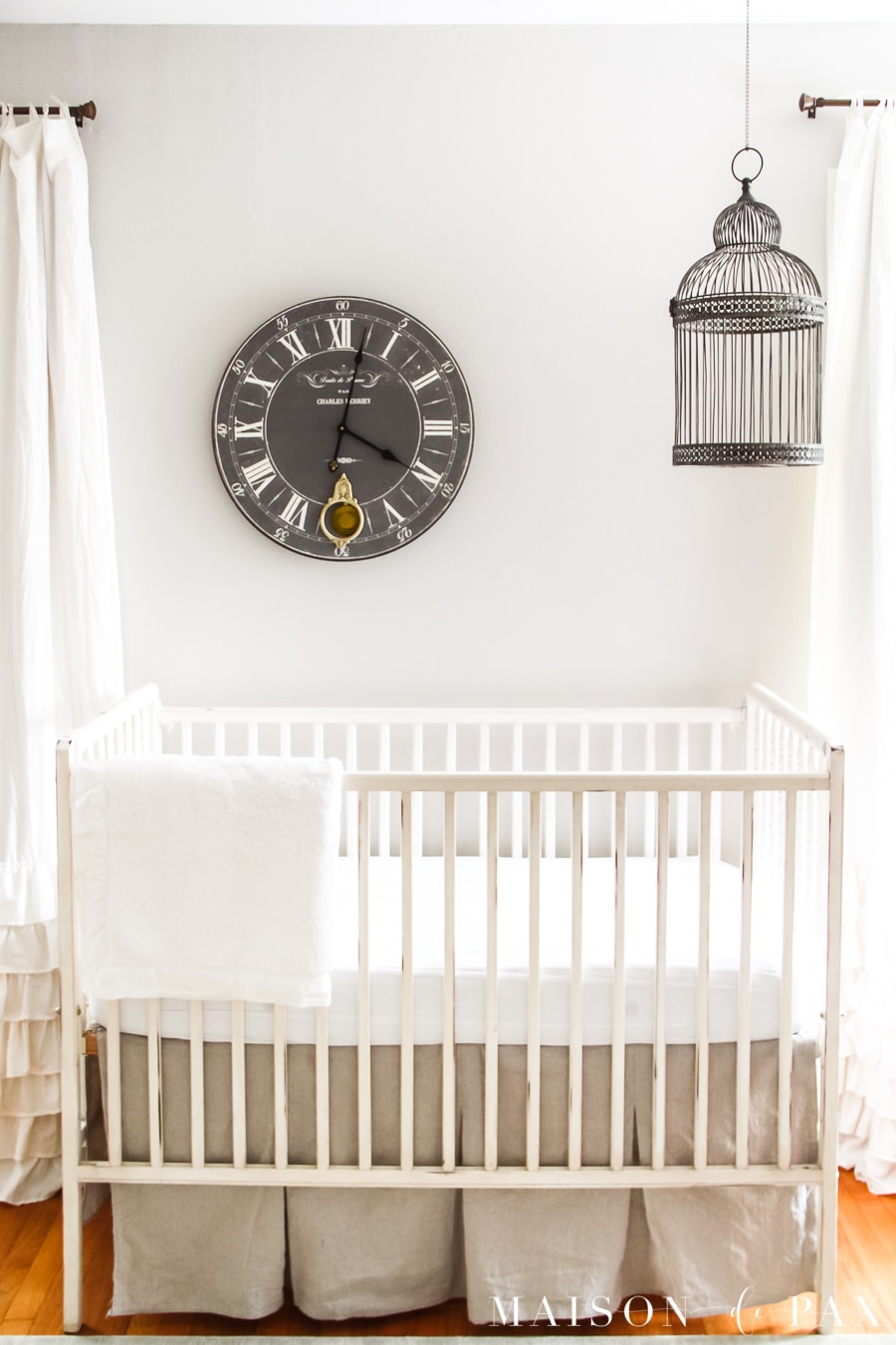 Nursery with antique white crib and curtains and SW Agreeable Gray walls | Maison de Pax