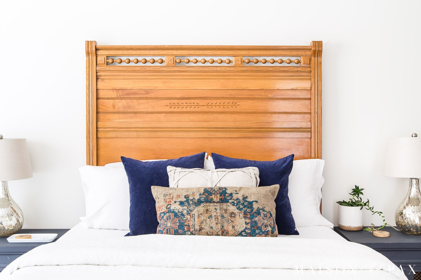 american antique wood headboard with crisp white linen bedding and velvet pillows | Maison de Pax