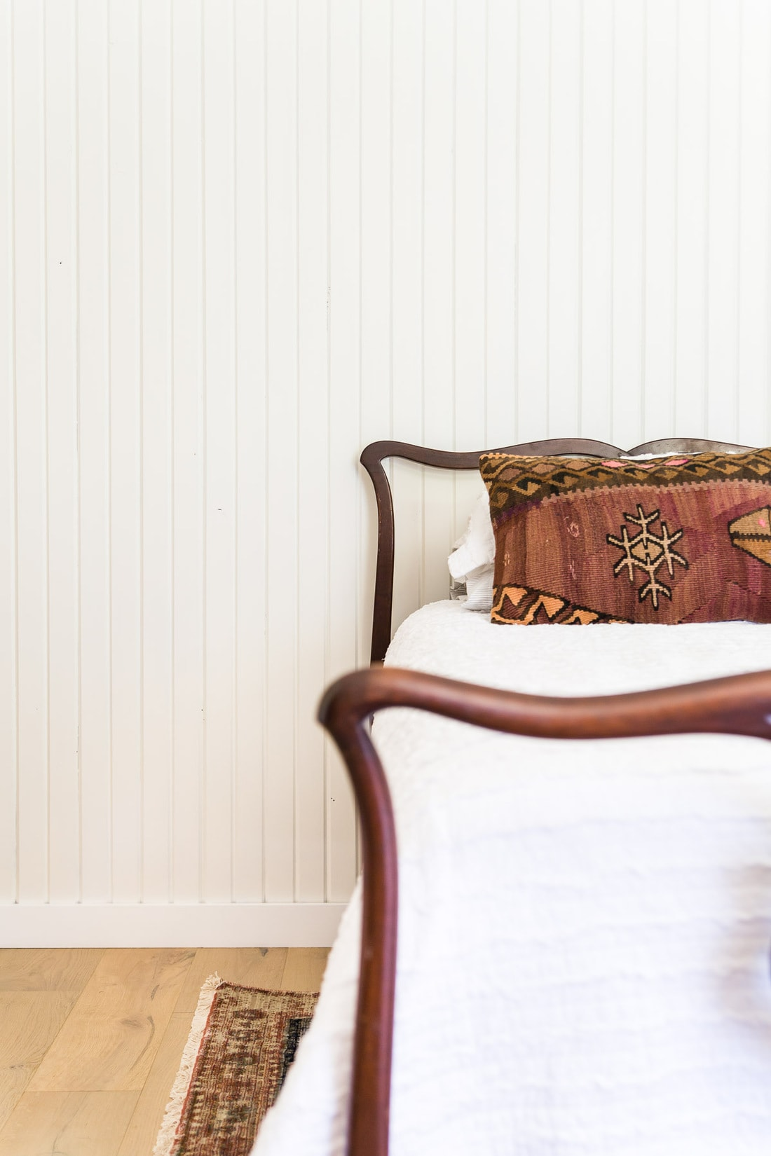 white painted vertical skinny shiplap walls with antique bed   Maison de Pax