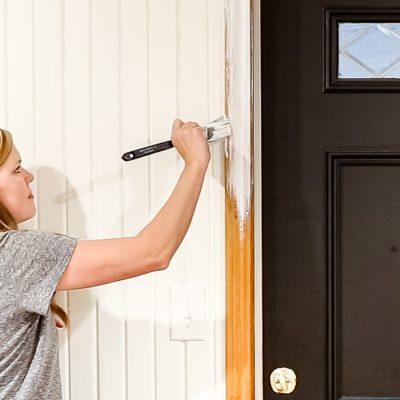 woman painting wood trim white   Maison de Pax