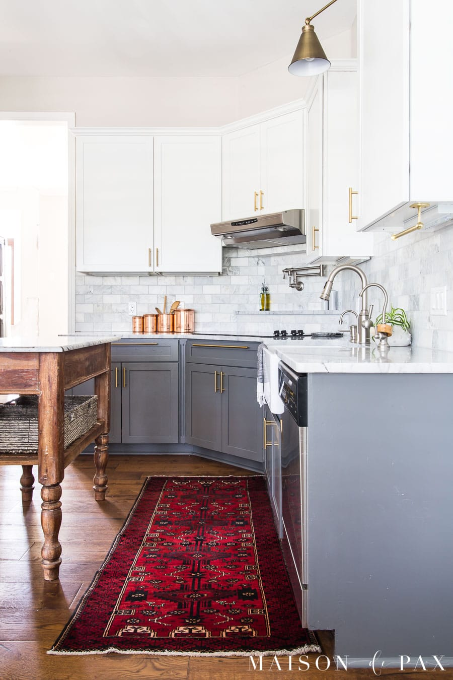 red vintage runner by kitchen sink and copper canisters on marble counters | Maison de Pax