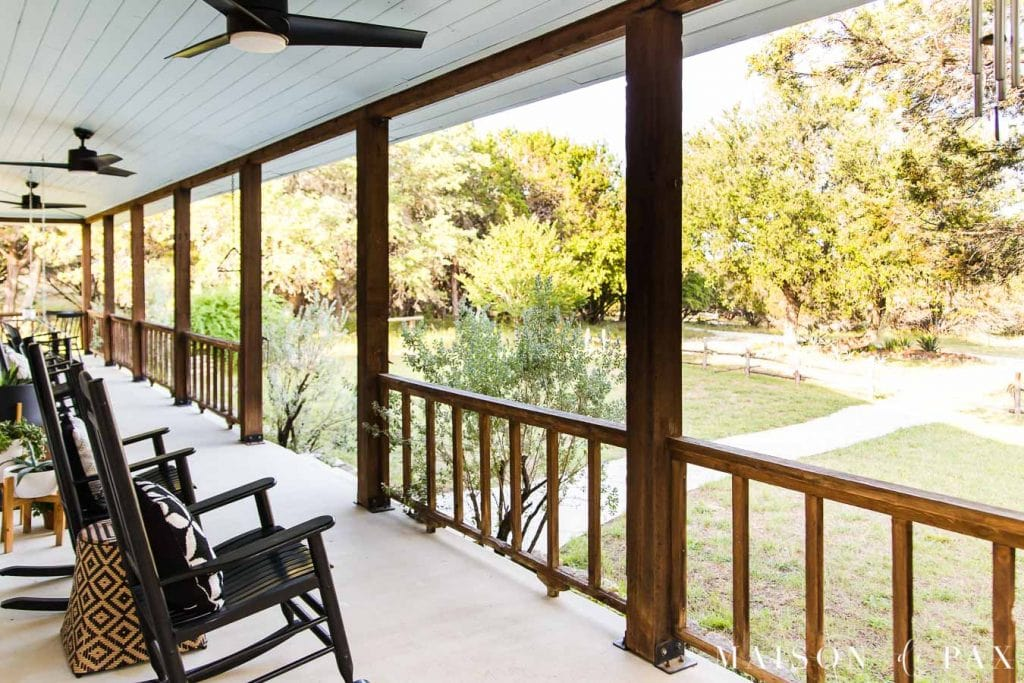 rocking chairs and a cedar porch railing overlook a texas hill country ranch | Maison de Pax