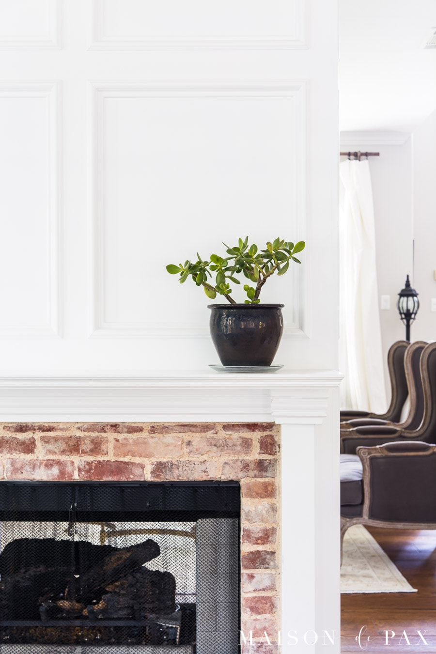 jade plant in black pot on white fireplace mantel | Maison de Pax