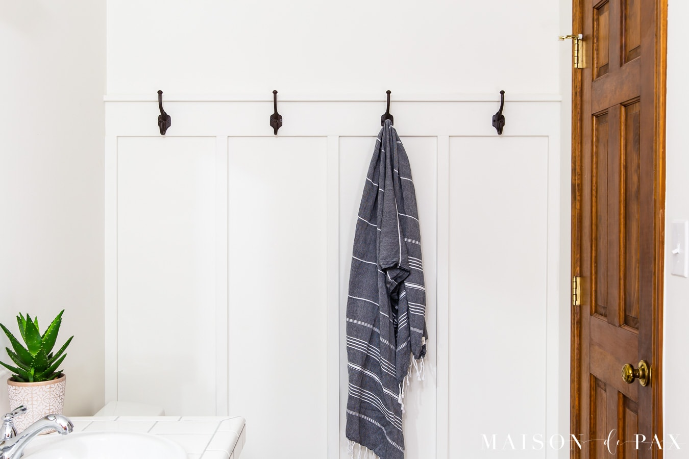 board and batten accent wall with towel hooks | Maison de Pax
