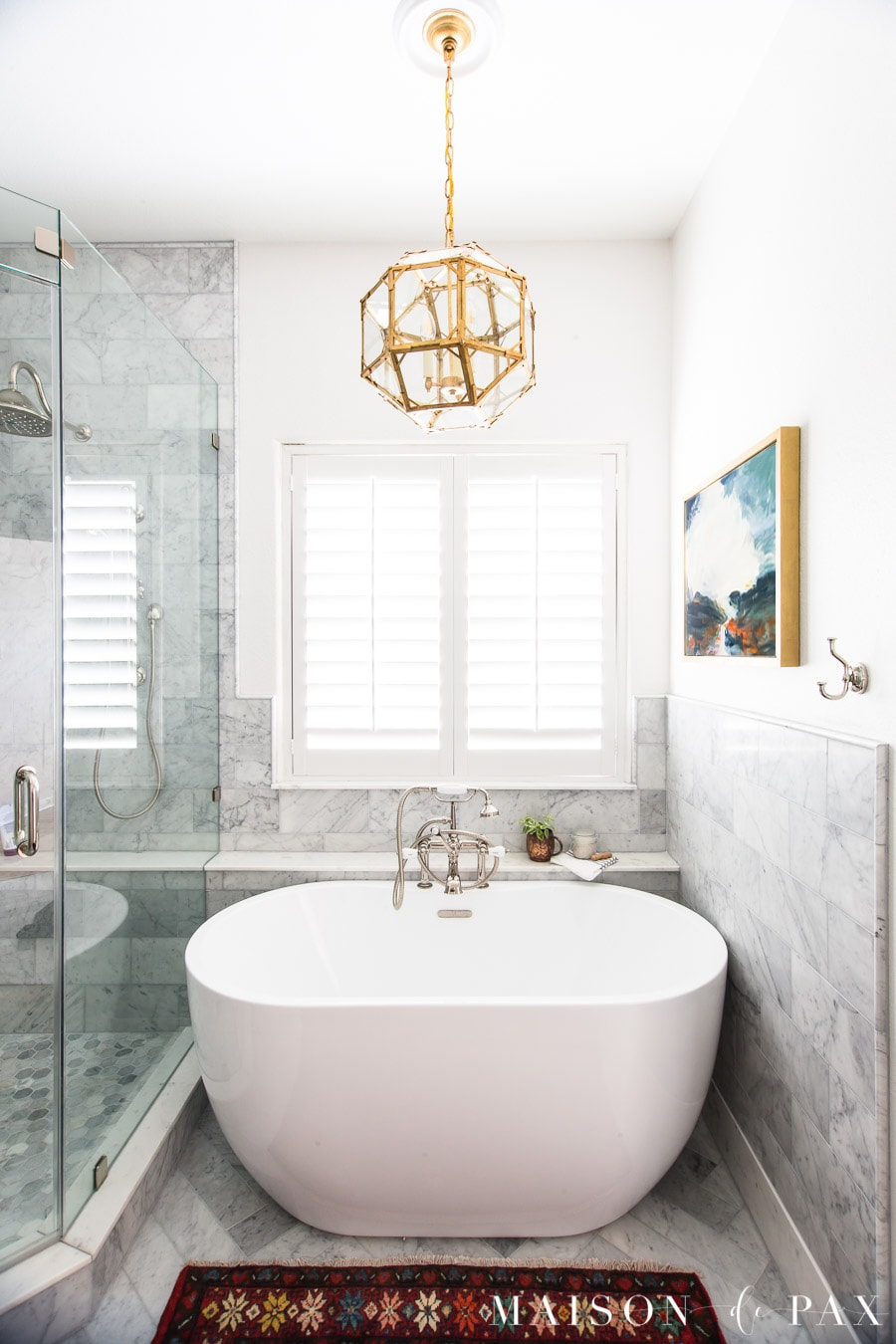 freestanding tub in marble bathroom with vintage rug and abstract art   Maison de Pax