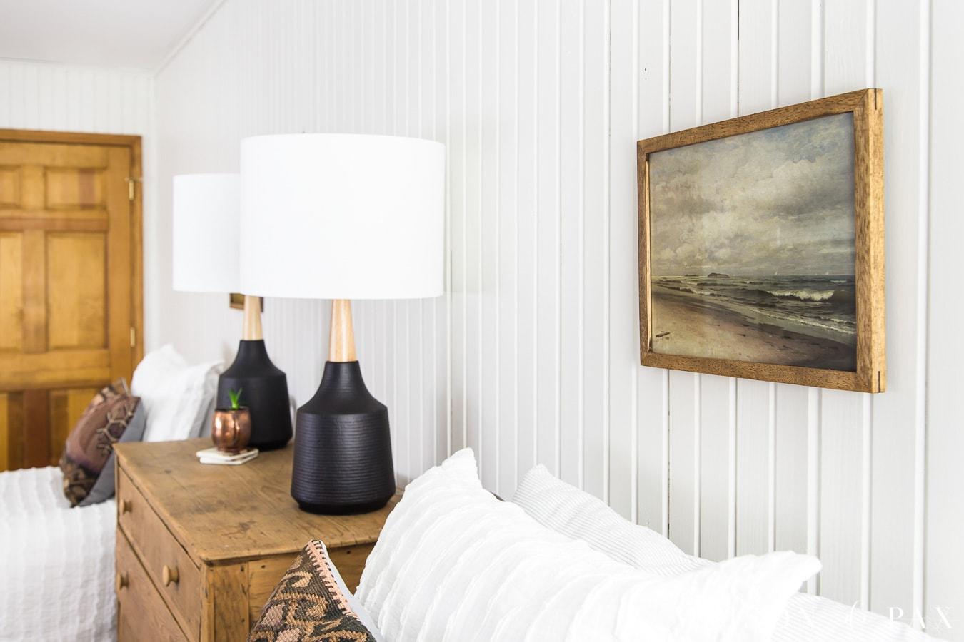 vintage beach landscape art above antique bed against white planked walls | maison de pax