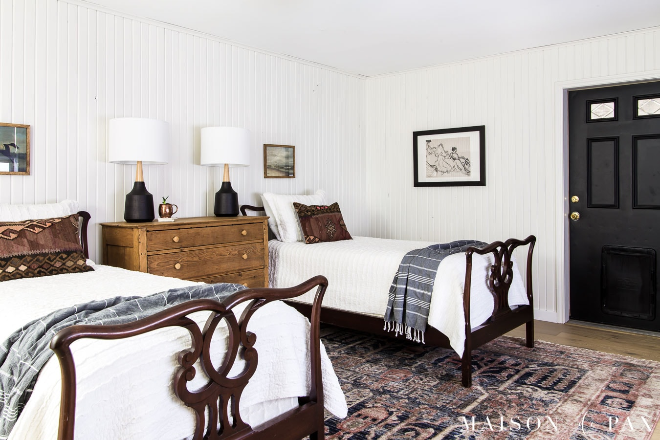 twin bedroom with white planked walls, vintage furniture, and colorful accents | Maison de Pax