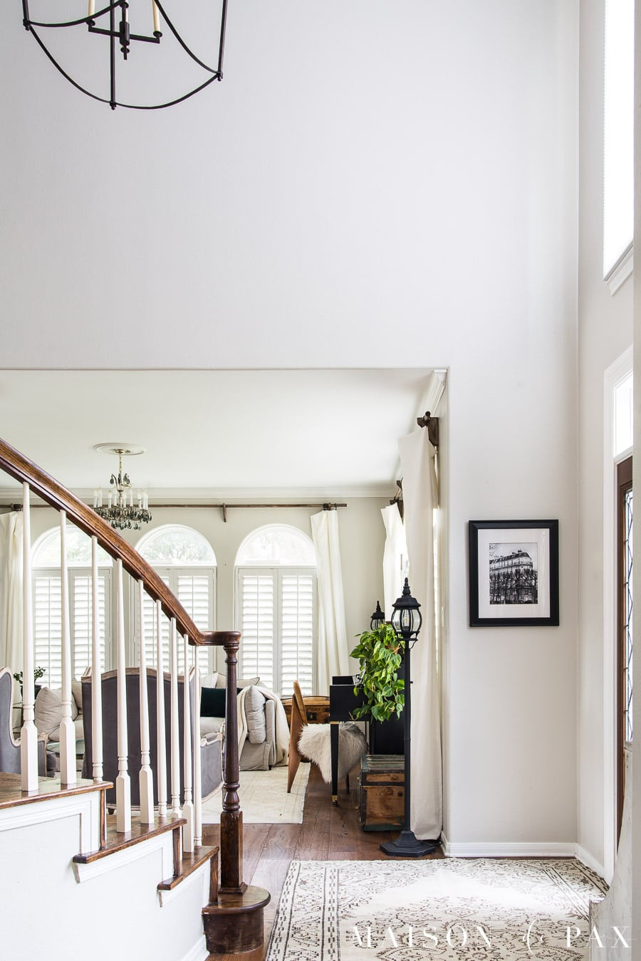 two story entryway and stairwell with large black lantern and vintage rug | Maison de Pax